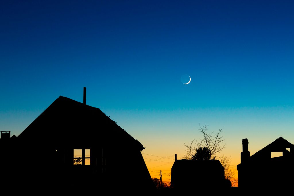 Houses roofs against the night sky with new moon